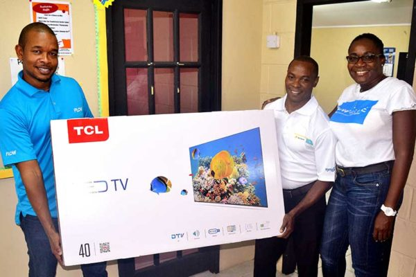 Image: Flow customer Fleming Jn. Paul (centre) won himself a brand new TCL TV!