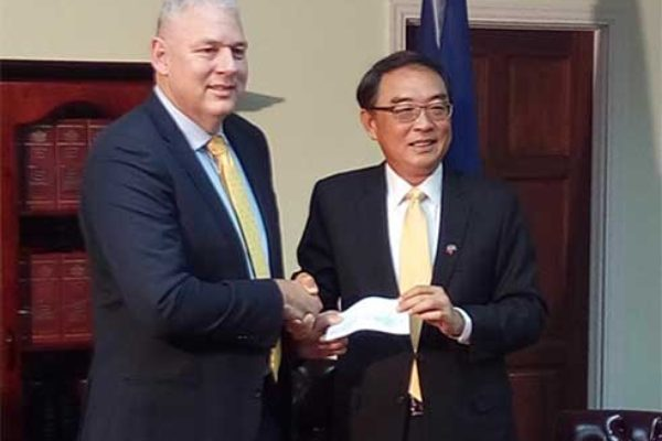 Image: P.M. Chastanet and Ambassador Shen at Thursday's cheque handing-over ceremony. (PhotoMike)
