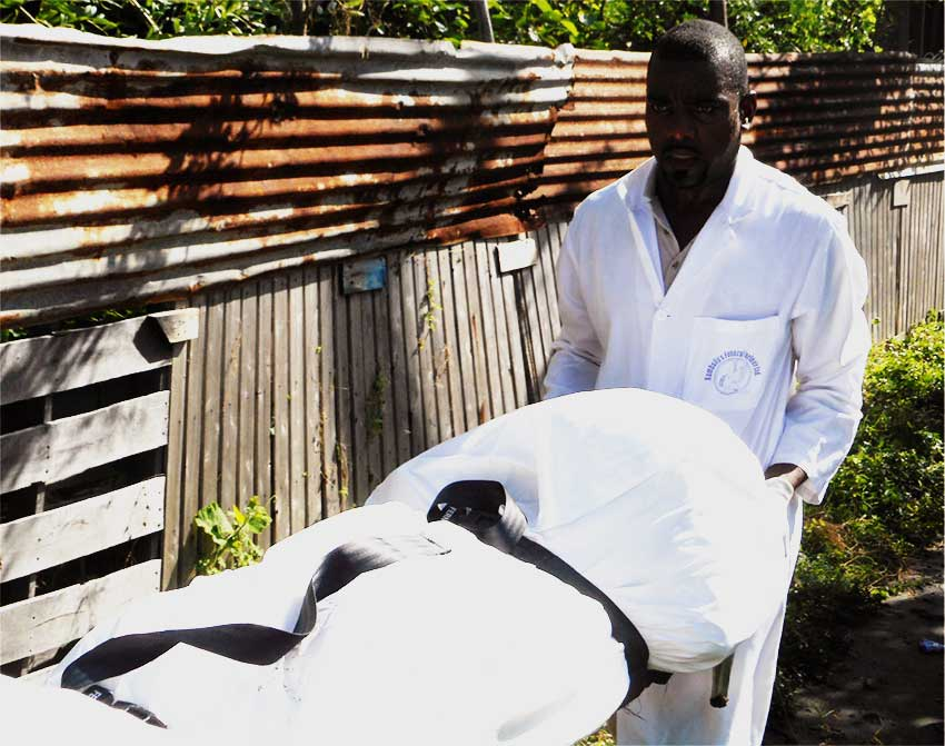 Image of Rambally Funeral Parlour staff removing one of the bodies.