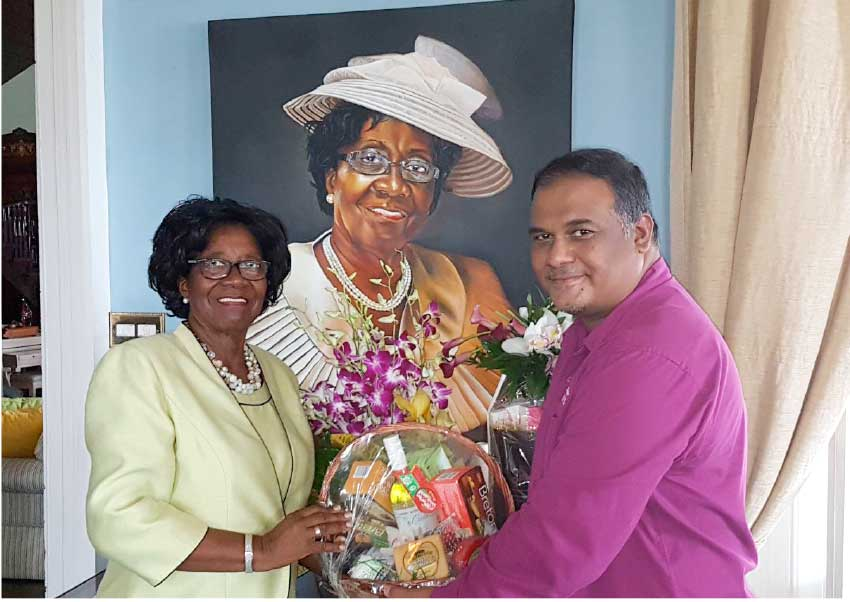 Image of Regional Public Relations Manager, Sunil Ramdeen, presenting tokens to Dame Pearlette Louisy.