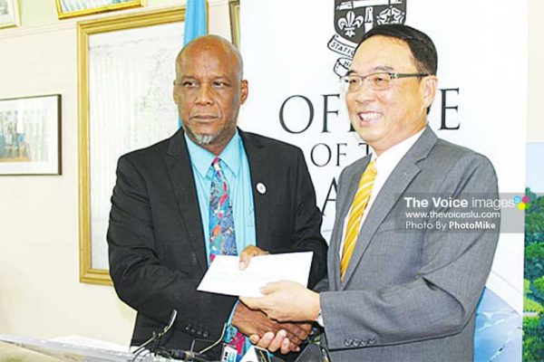 Image: Castries Mayor Peterson Francis receives the cheque from Taiwanese Ambassador Douglas Shen last Thursday. (PhotoMike)