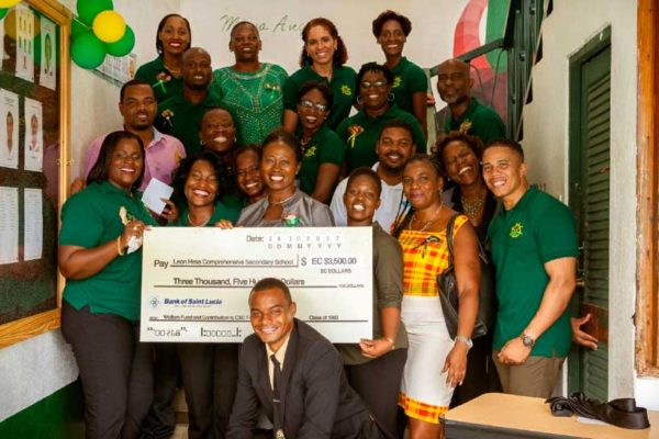 Image: Group photo with cheque, next to newly-unveiled noticeboard at the school.