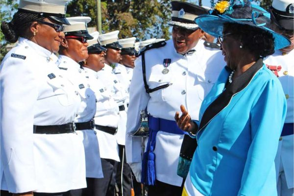 Image: Dame Pearlette chatting with a female police officer on parade accompanied by Assistant Commissioner of Police Frances Henry, the highest ranking female officer of all time in the police force who sometimes wears the hat of acting Deputy Police Commissioner. (PHOTO: PhotoMike)