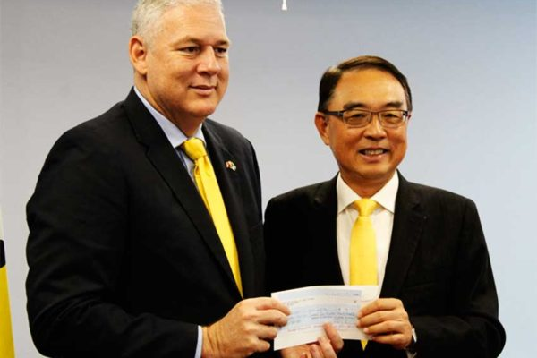 Image of Prime Minister Allen Chastanet accepting a cheque for EC$180,000 from Taiwanese Ambassador to St. Lucia, Douglas Shen