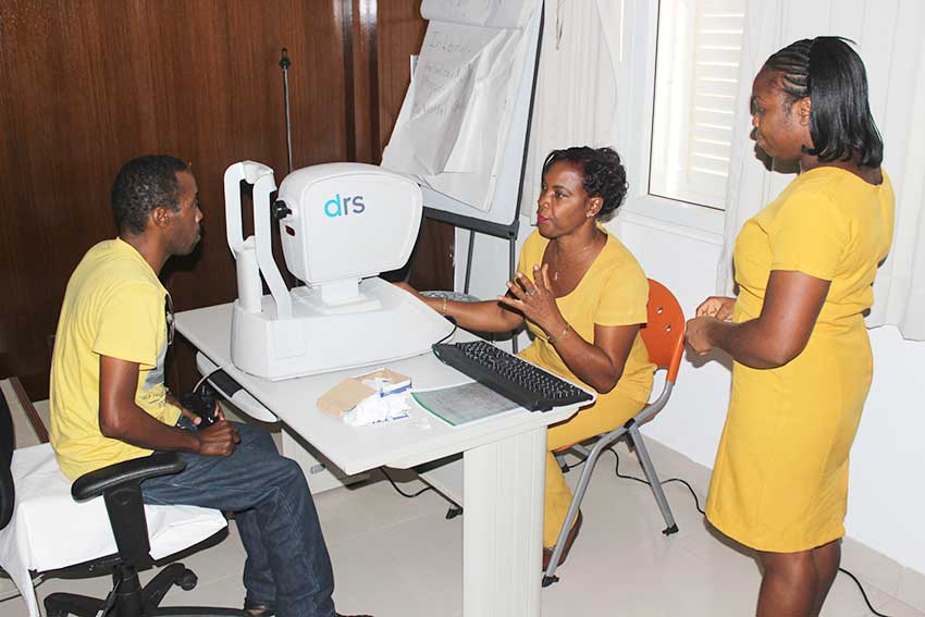 Image of Workshop participants checking a patient's eyesight.