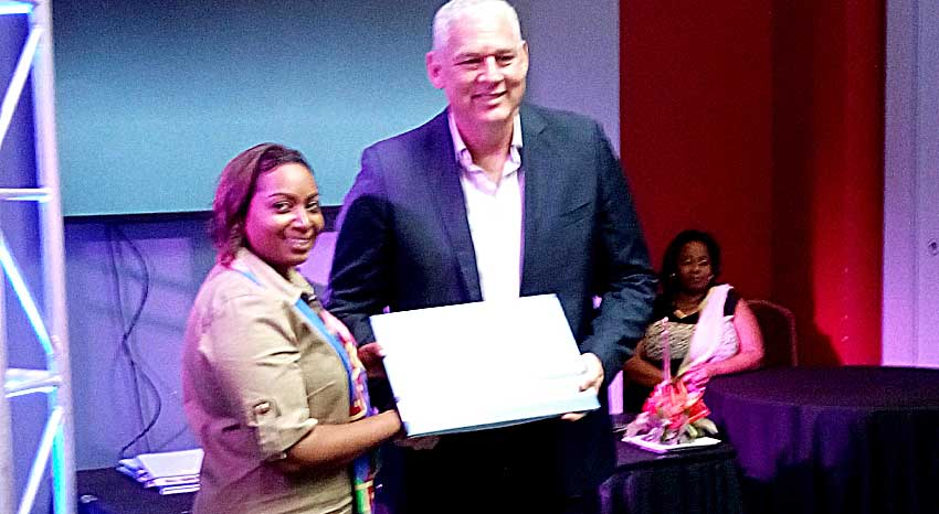 Image of Rambally presenting a copy of her new book to Prime Minister Allen Chastanet.