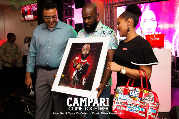 Image of Campari Caribbean's Regional Commercial Director Michelle Brown (right) presenting Bunji Garlin with his animated Campari Red Image.