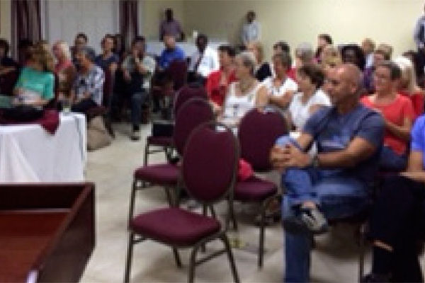Image: Members of the 100 Women and Men St. Lucia listen attentively to the charity presentation.