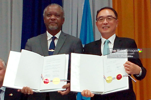 Image of Minister Francis (left) and Ambassador Shen holding up the signed documents. (PHOTO: PhotoMike)