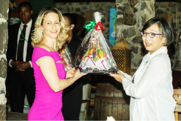Image of Mrs. Chastanet, left, presenting a local token of appreciation to the guest of honour.