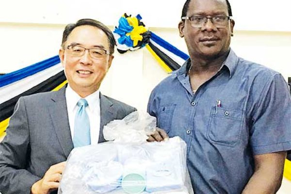 Image of His Excellency Ambassador Douglas Shen handover the sample of charity supplies to the Honourable Lenard Montoute