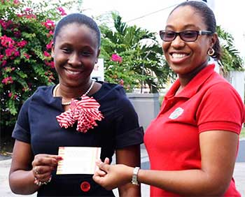 Image: (L-R) DarnicaJn Charles receiving her Jazz tickets from RUBIS West Indies Limited's, ChriseldaNorbal, Assistant Account Executive. (PHOTO: RUBIS)