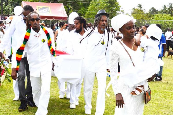 Image: Tafari's mother Marilyn Martin Charlemange leads the cortege onto the field; Tafari's coffin in open air at the LCPF (Photo: Anthony De Beauville)