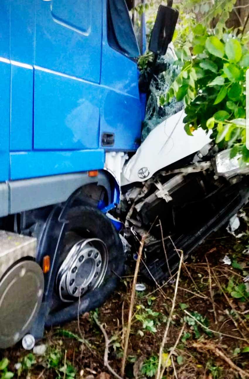 Image of Minibus mangled under lorry