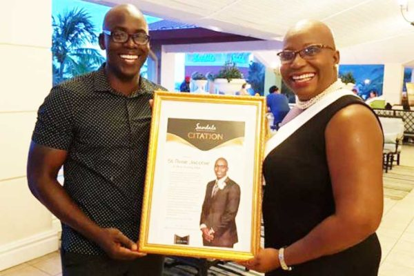 Image of a Beaming St. Rose Jacobie receives his Citation from Minister Gale Rigobert