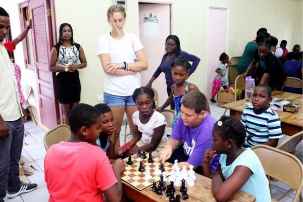 Image of Brandon Chastanet (3rd from right) sharing chess moves down south!