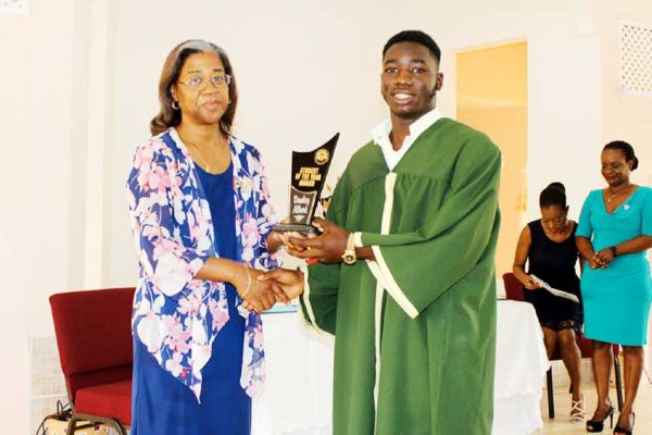 Image of Health Minister Mary Isaac congratulating the winning student.