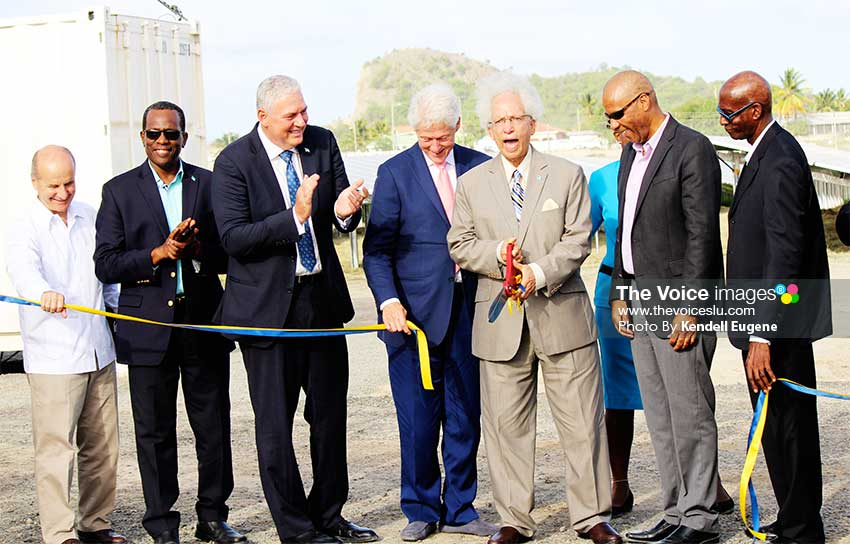 Image: OPEN SESAME! The Prime Minister, Opposition Leader, President Clinton, LUCELEC Managing Director and Board Chairman in joint applause as Governor General Sir Winston Cenac cuts the ribbon at La Tourney to launch the island's First Solar Farm. (PHOTO: Kendell Eugene)