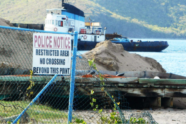 Image of the usual berth of the Southern Marine Police vessel is now empty against the background of a rising mountain of sand.
