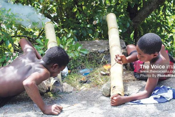Image: These two young Saint Lucians in Canaries were among many keeping the bamboo-bursting tradition alive Sunday around the island. (Photo by: PhotoMike).