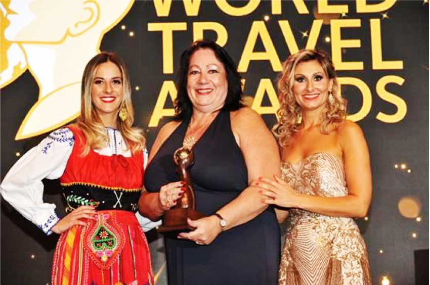 Image of Deana Stefano (centre), Office Manager at Unique Vacations UK Ltd, accepting award on behalf of Sandals Resorts International (SRI).