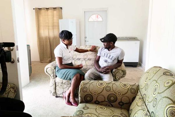 Image: Digicel Marketing Manager Jamisha Wright and $15,000 grand prize winner of a home makeover Leon Brin have a quick chat on his brand new sofa