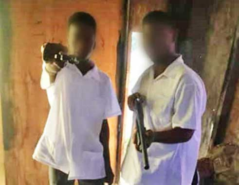 Image: Two boys pictured in full secondary school uniform with what appears to be firearms (a hand gun and shot gun).