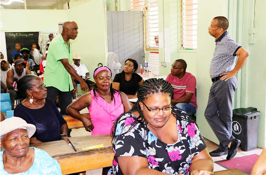Image of WASCO's Strategic Planning Manager (R-standing) listening attentively to a resident