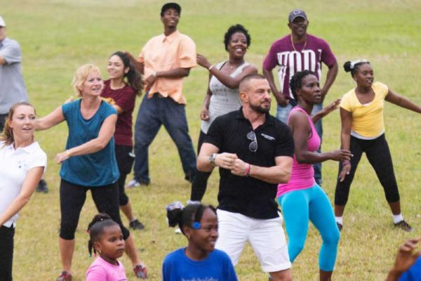 Image of the BodyHolday team dancing away with residents of Monchy.