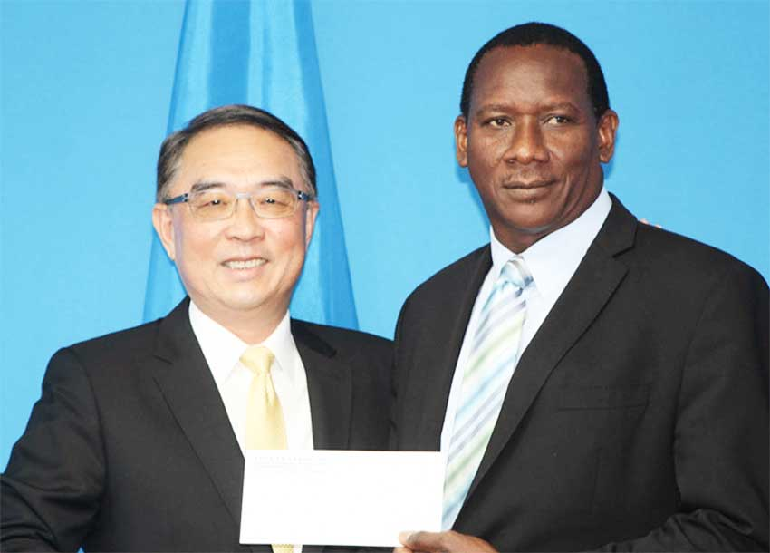 Image of Taiwanese Ambassador to Saint Lucia His Excellency Douglas Cheng and Minister for Equity, Social Justice, Local Government and Empowerment Lenard Montoute displaying one of two cheques representing Taiwan's generosity to the country's Constituency Development Programme (CDP).