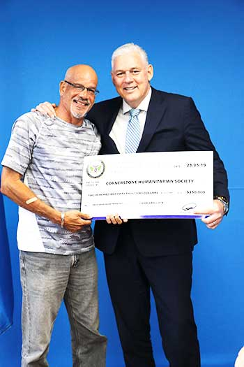 Image of Cornerstone's Mr. Desmond Phillip receiving donation of $250, 000 from Prime Minister Hon. Allen Chastanet
