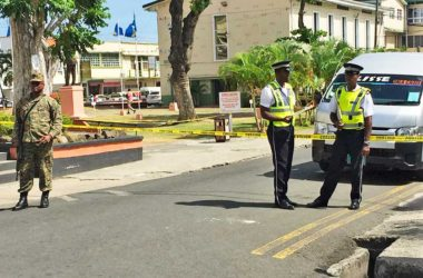 Image: Police officers stand guard near the First District Court where the bomb threat was made.