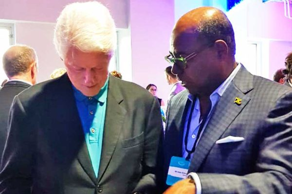 Image of Jamaica's Tourism Minister Ed Bartlett speaking with former US President Bill Clinton at the Clinton Global Imitative in the USVI.
