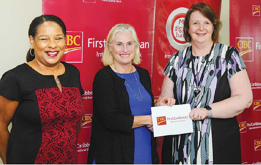 Image: Executive Director and co-founder of Hands Across the Sea, Mrs. Harriet Linskey, second from left receiving the donation cheque from Chief Executive Officer of CIBC FirstCaribbean International Bank and Chairperson of the ComTrust Foundation, Ms. Colette Delaney. Looking on is Mrs. Debra King, the bank's Director of Corporate Communications and Director of ComTrust Foundation