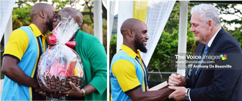 Image: (L-R) Javelin thrower Albert Reynolds gets a hug and a fruit basket from SLOC President Fortuna Belrose; Saint Lucia's Prime Minister Allen Chastanet extends his hospitality to Reynolds with a weekend for two at the Coco Palm Hotel. (Photo: Anthony De Beauville)