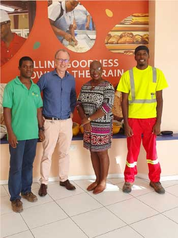 Image of Managing Director of Caribbean Grains Ltd, Arnaud de Moussa (second from left) and Minister Dr Gale Rigobert with Caribbean Grains team members.