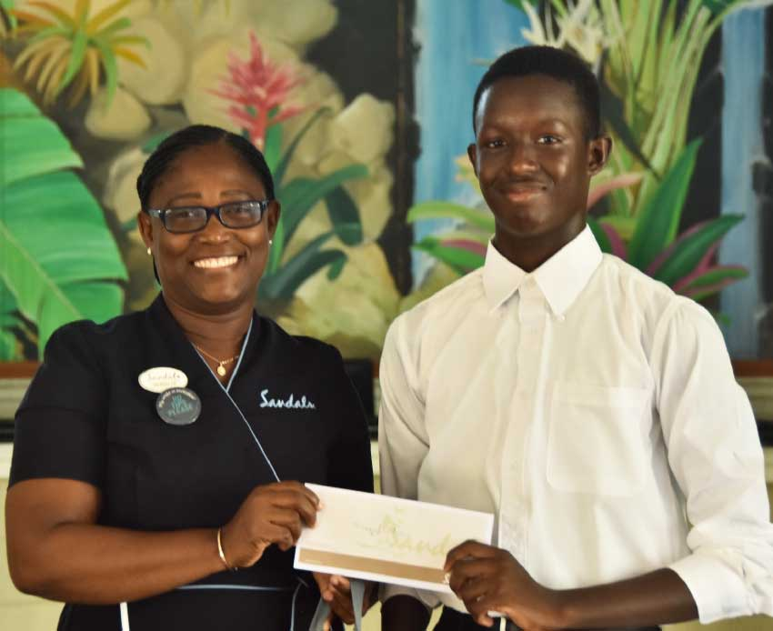 Image: Shaquil Flavius receiving his scholarship pack from Versilia Jn Baptiste, Front Office Supervisor, Sandals Halcyon Beach Resort.