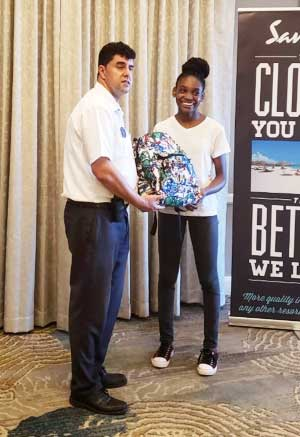 Image of Tiffany Florent receiving her Sandals Foundation scholarship from Rui Freitas, Hotel Manager, Sandals Regency La Toc Golf Resort & Spa.