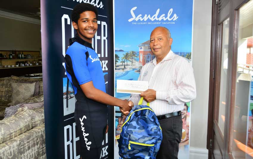 Image: Xaviour Blanchard receives his Sandals Foundation scholarship from the Managing Director of Sandals Resorts in Saint Lucia, Winston Anderson.