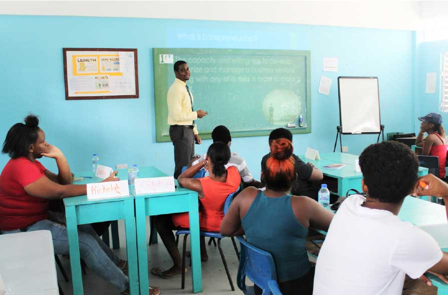Image: ISL's Communications and Marketing Assistant, Yves Peter mentoring youth on entrepreneurship.
