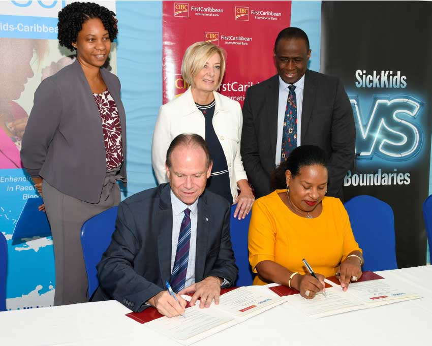 Image: CEO of SickKids Foundation Ted Garrard and Debra King, Director of Corporate      Communications, CIBC FirstCaribbean sign the new MOU witnessed by SickKids                Fellow Dr Chantelle Browne-Farmer (back left) Bonnie Fleming-Carol, Associate Chief of Nursing & Inter-professional Education at SickKids (centre) and Dr Upton Allen, Chief of the Division of Infectious Diseases at SickKids.