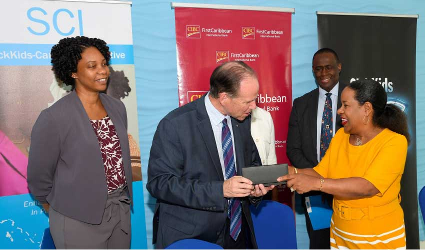 Image: Debra King, Director of Corporate Communications, CIBC FirstCaribbean presenting CEO of SickKids Foundation Ted Garrard with the pens used in the signing ceremony. Looking on is SickKids Fellow Dr Chantelle Browne-Farmer (back left) Bonnie Fleming-Caro (partly hidden), Associate Chief of Nursing & Inter-professional Education at SickKids (centre) and Dr Upton Allen, Chief of the Division of Infectious Diseases at SickKids.