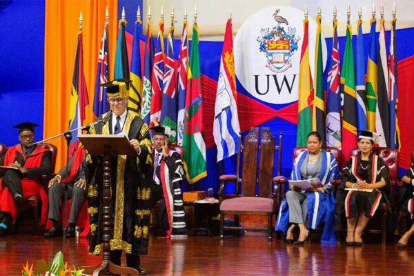 Image: Chancellor Robert Bermudez addressing the company as members of the UWI Executive on the platform look on.