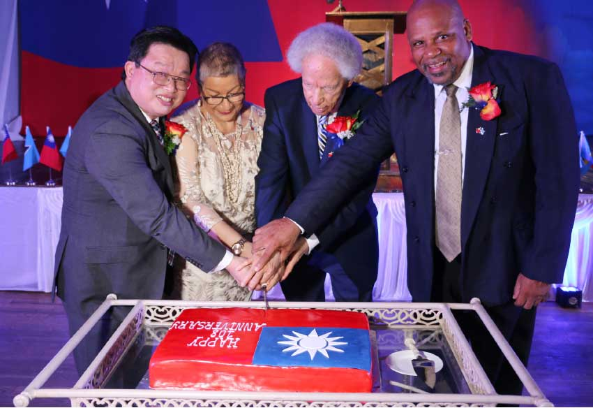 Image: The joining of hands during the cake cutting. From left: Charge d'Affaires at the Embassy of Taiwan Bill Shih-Chang Huang, Lady Cenac, Governor General Sir Neville Cenac and Minister Ezechiel Joseph.