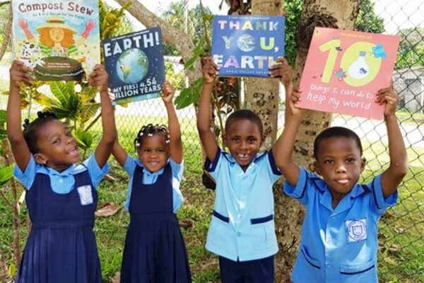 Image of Students at Moneague Teachers' College Basic School in Jamaica, share bright smiles after taking part in a reading session with environmental books.