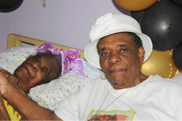 Image of Angela Williams (left) with her daughter Mary Etienne at her home in Old Belair last Sunday.