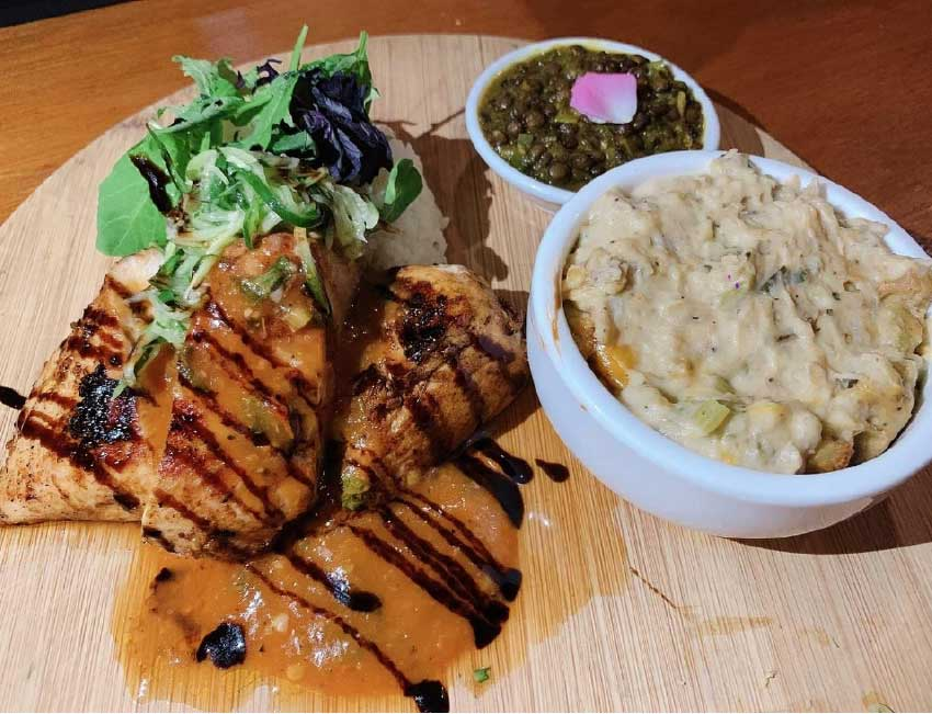 Image: Beer batter roasted chicken with coffee BBQ sauce served with green banana gratin, coconut herb rice, fresh cucumber salad and Lucian style lentils.