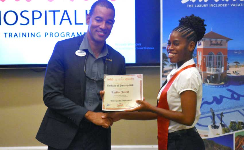 Image: Christopher Elliott, General Manager at Sandals Halcyon awarding certificate to graduate.