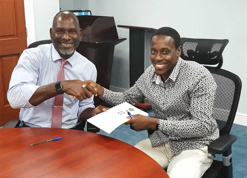 Image: Contractor Lwanga Willie signs his contract for drainage works in Desruisseaux with Mr. Claudius Emmanuel, Permanent Secretary of the Ministry of Economic Development, Housing, Urban Renewal, Transport and Civil Aviation under which the DVRP falls.