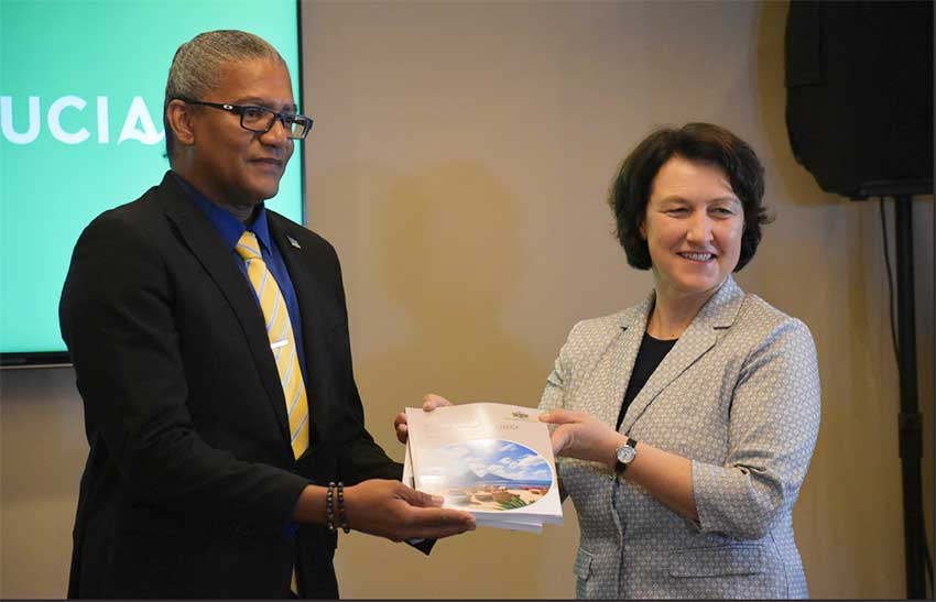 Image of ITC Director and Chief Economist Marion Joseph (R) handing o Commerce Minister Bradley Felix the NES docunment.